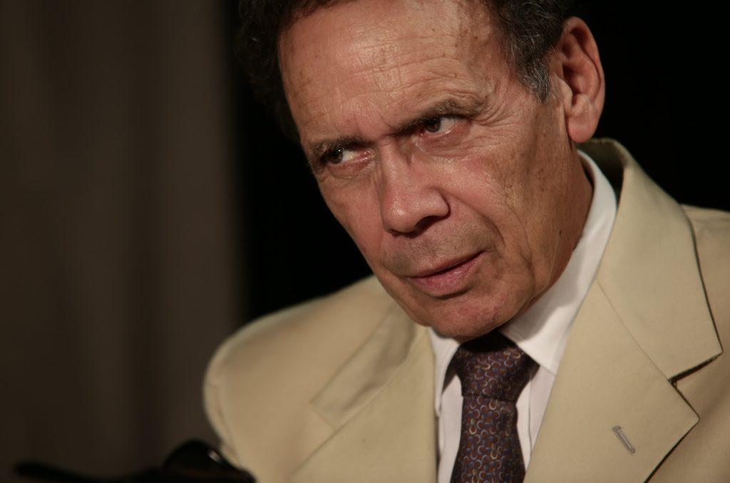 storia L'attore che interpreta Buscetta con camicia bianca cravatta scura e impermeabile beige nella piece teatrale che narra la storia del boss dei due mondi