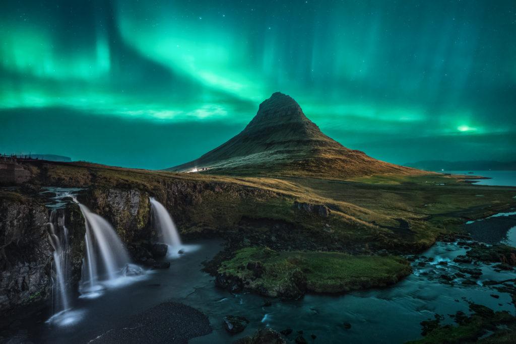 l'aurora boreale in °Islanda con un cielo che si colora di verde e il paesaggio sembra lunare, con cascate di acqua e torrenti azzurro viola
