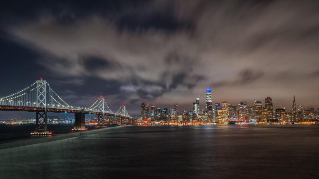 una veduta di San Francisco in una foto di matteo bertetto che in un intervista ci spiega la sua tecnica per fotografia moderna Il ponte illuminato e la città sullo sfondo, un cielo notturno quasi apocalittico