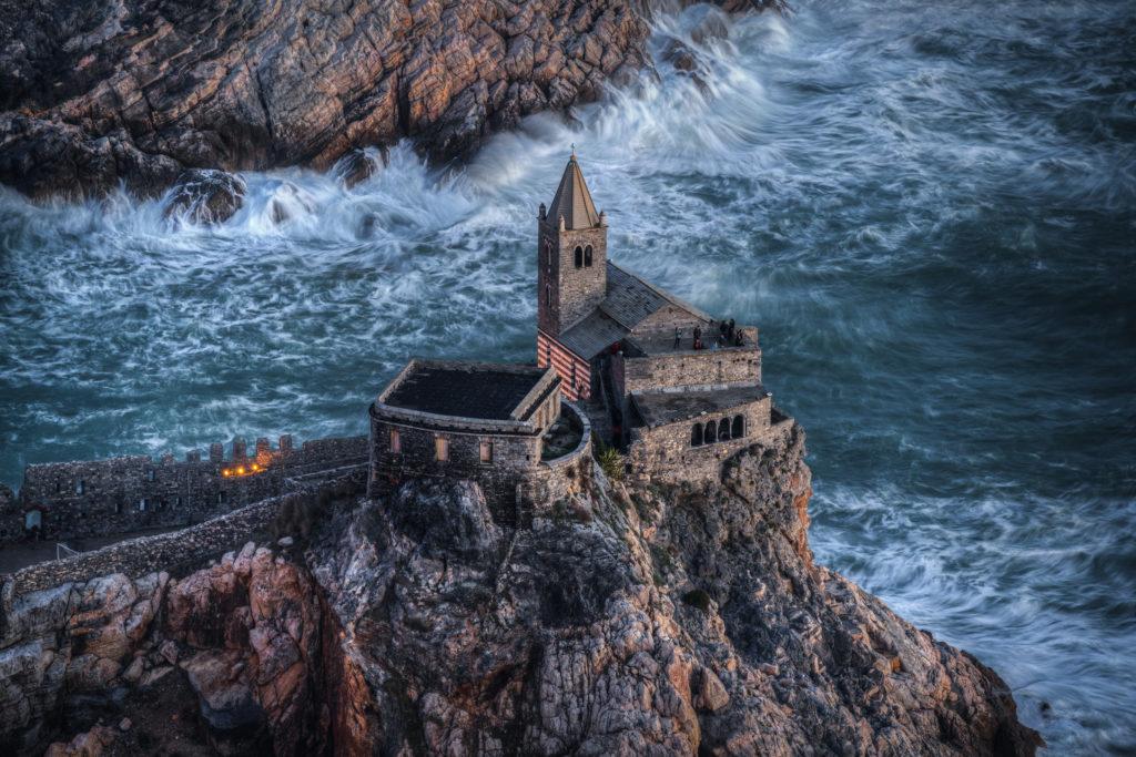 Una veduta dall'alto di San Pietro in Porto Venere, realizzata con la tecnica di fotografia moderna di Matteo Bertetto, una rocca con in cima una castello e il mare in burrasca intorno