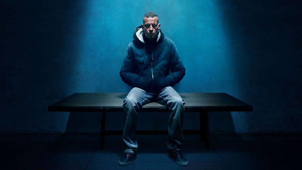 la locandina della fiction netflix sul processo del caso stefano cucchi e la sua storia, con un uomo vestito con jeans e giubbotto blu, seduto su un apanca del carvere, con le mani in tasca e solo una luce blu che lo illumina