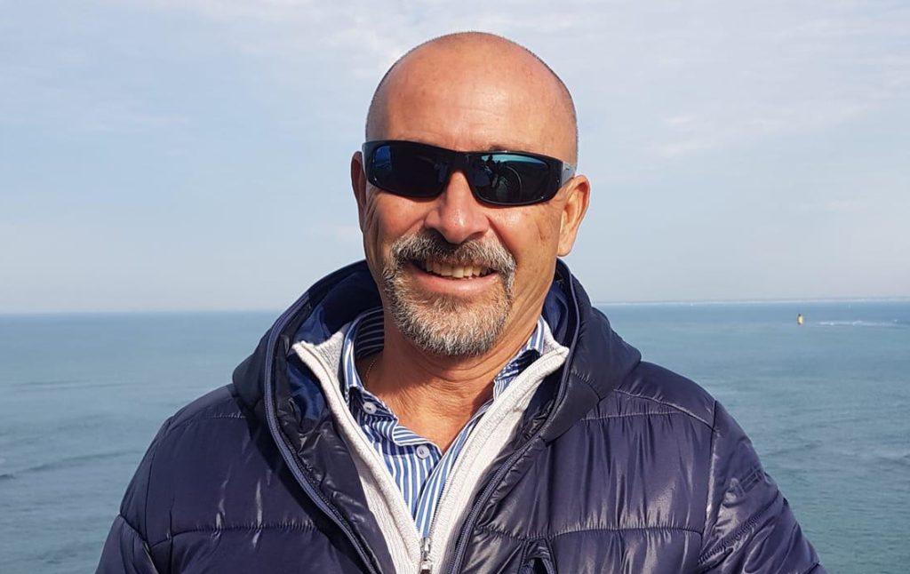Americo Pilati, presidente di federalberghi liguria, calvo, con occhiali da sole neri, sorridente, con pullover bianco e piumino blu, sullo sfondo il mare