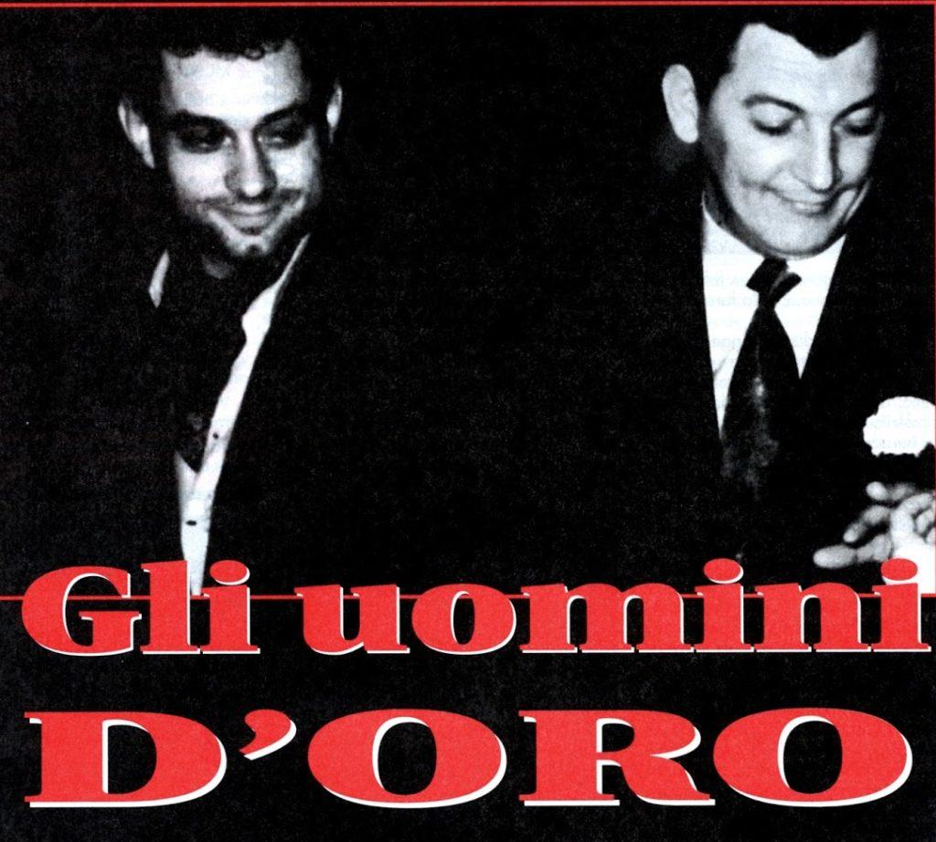 Gli uomini d'oro: foto in bianco e nero da sinistra Giuliano Guerzoni e Enrico Ughini entrambi con camicia bianca e giacca nera, Ughini sorride e ha un garofano all'occhiello