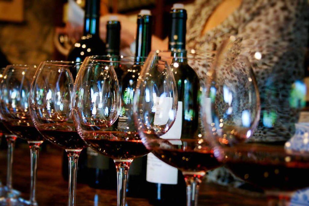 Dei bicchieri a calice in fila, con del vino brunello , davanti ad alcune bottiglie di vino