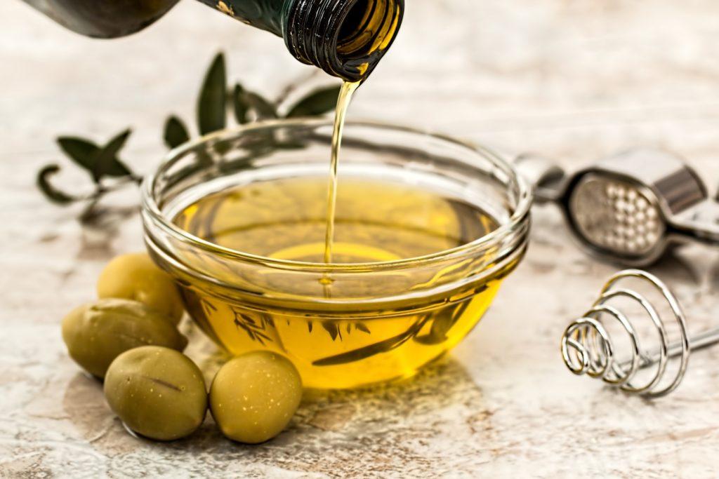 meet in cucina marche . Una bottiglia d'olio riempie una ciotola e intorno delle olive e degli attrezzi da cucina