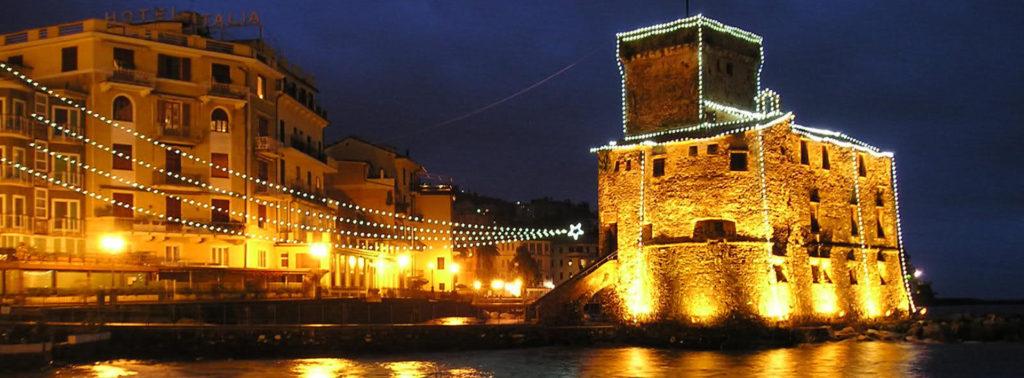 vista notturna di una località di mare addobbata con luci di Natale