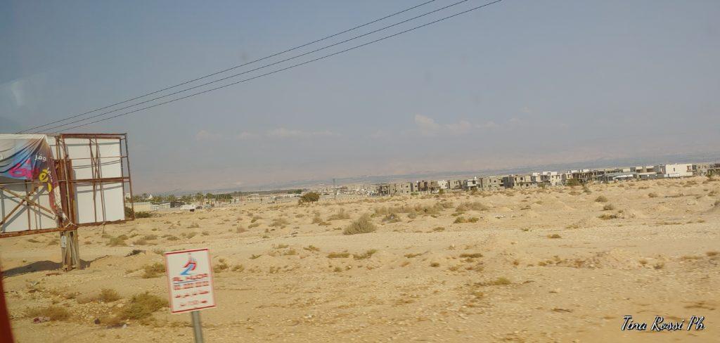 il deserto dove jesus venne tentato, con un pannello pubblicitario sulla sinistra e sullo sfondo una città
