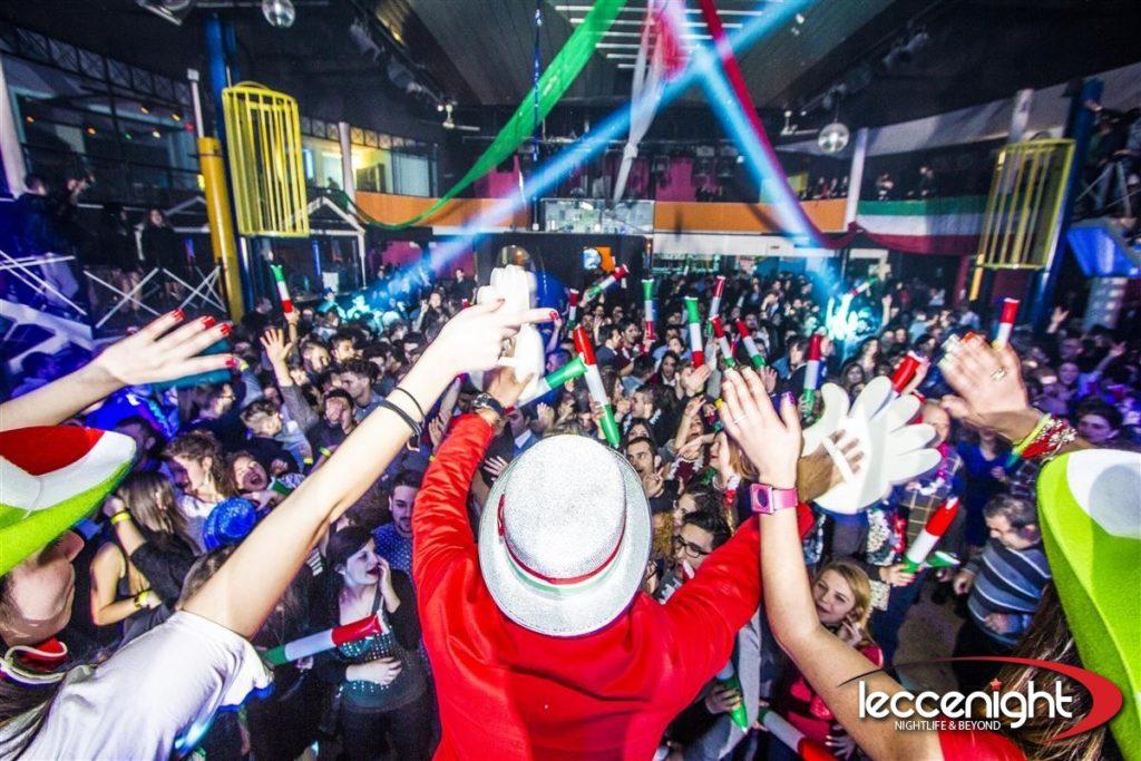 Capodanno in discoteca piena di gente che sventola tubi tricolore italiano
