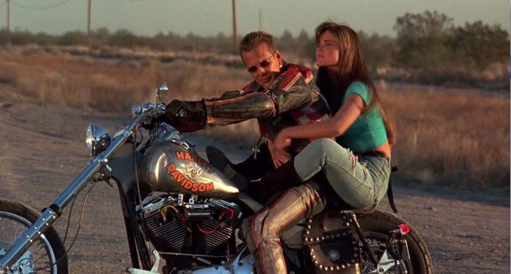 Mickey Rourke in una scena del film Harley-Davidson e Marlboro man, in sella alla moto insieme ad una ragazza