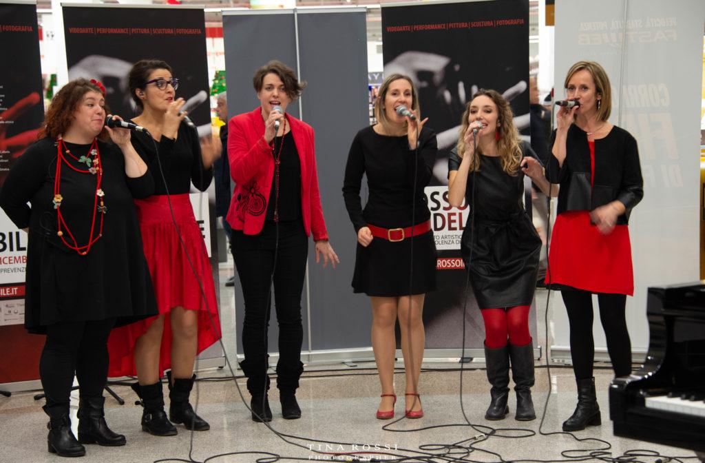 le Vocal Boutique vestite di rosso e nero mentre cantano a cappella dal vivo
