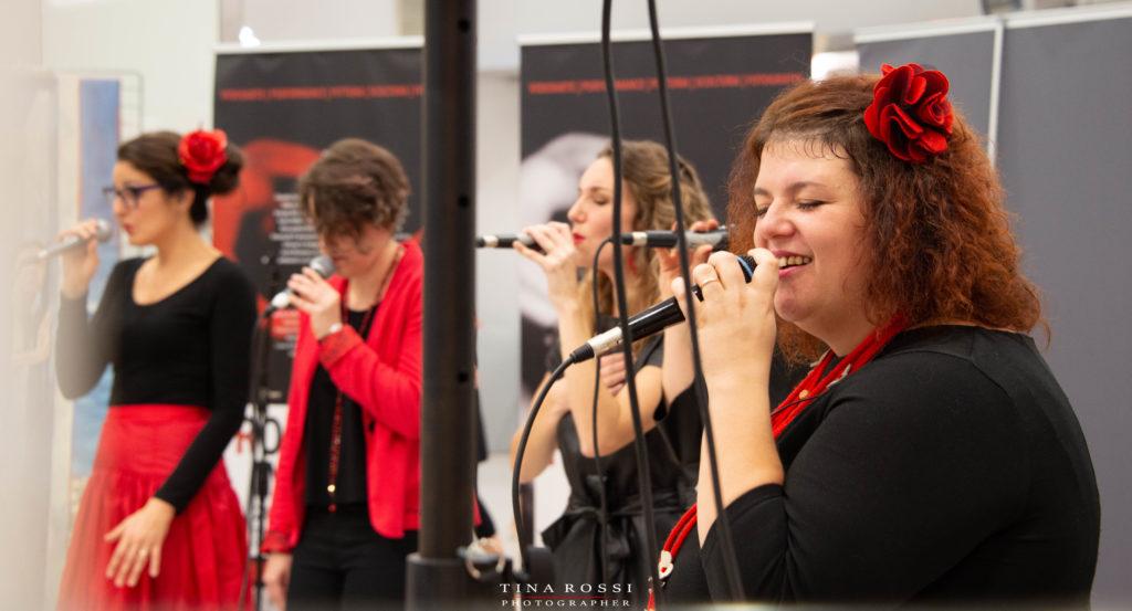 Tre componenti del gruppo vocal boutique una bionda in primo piano e le altre due more vestite di nero cantano a cappella