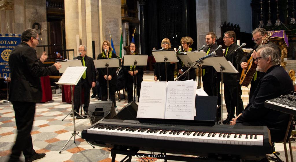 Il coro del Duomo di torino,. diretto dal maestro d'orchestra con in primo piano una tastiera