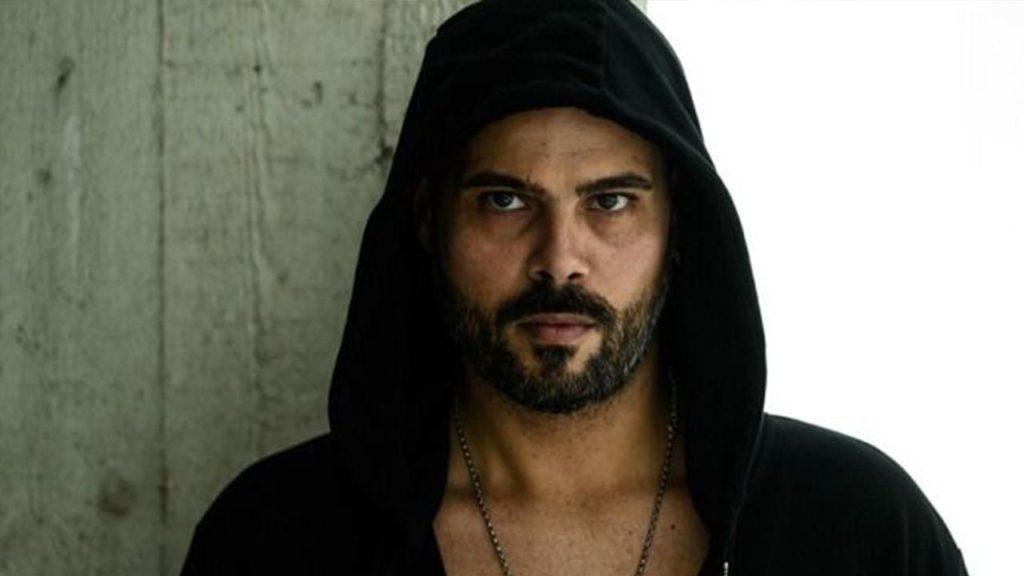 Immortale: primo piano di Marco D'amore, interprete del personaggio di Ciro Di Marzio. indossa una felpa nera con il cappuccio calcato sulla testa