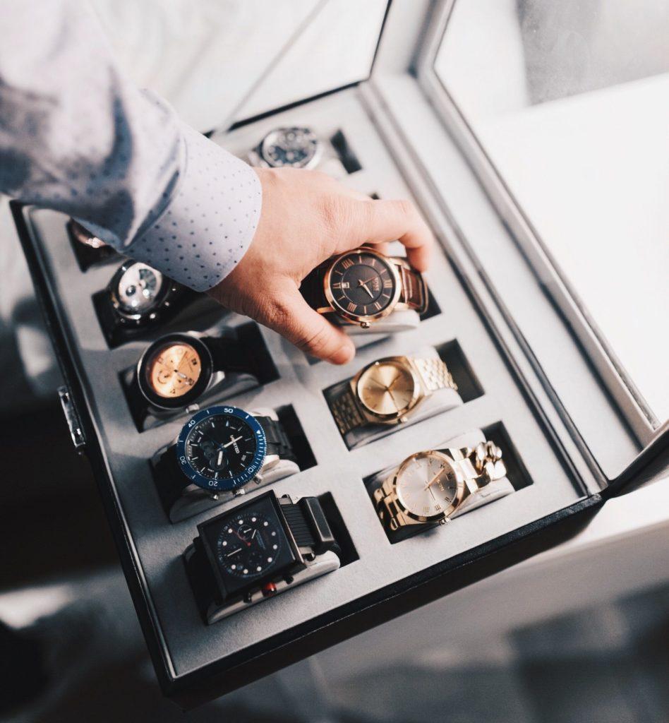 Una scatola piena di orologi costosi e una mano che ne ripone uno