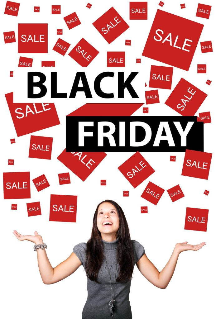 La scritta nera Black Friday con intorno tanti quadrati rossi con su scritto offerta, sale e una donna con le braccia rivolte al cielo, sorridente