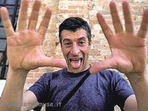 L'artista Maurizio Cattelan in maglietta azzurra che fa una boccaccia