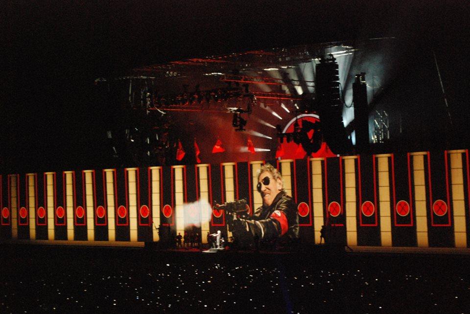 Pink floyd the wall: immagine del concerto di Roger Waters, che lo vede impugnare un mitra davanti al muro, vestito con un lungo cappotto di pelle nera