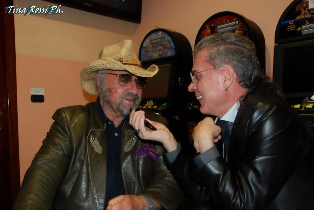 Pietruccio Montalbetti e il direttore di Zetatielle, ripresi durante un'intervista. Pietruccio indossa una giacca di pelle e un cappello di paglia da cawboy, lele boccardo una giacca di pelle nera