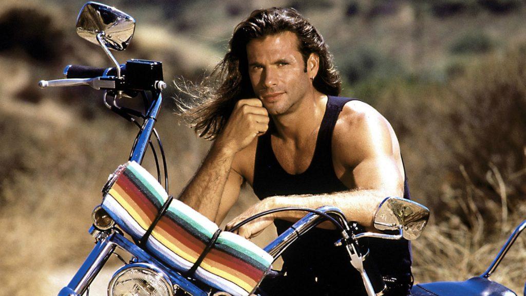 Harleysta: primo piano di Lorenzo Lamas, appoggiato al manubrio della sua Harley-davidson. indossa una canotta nera