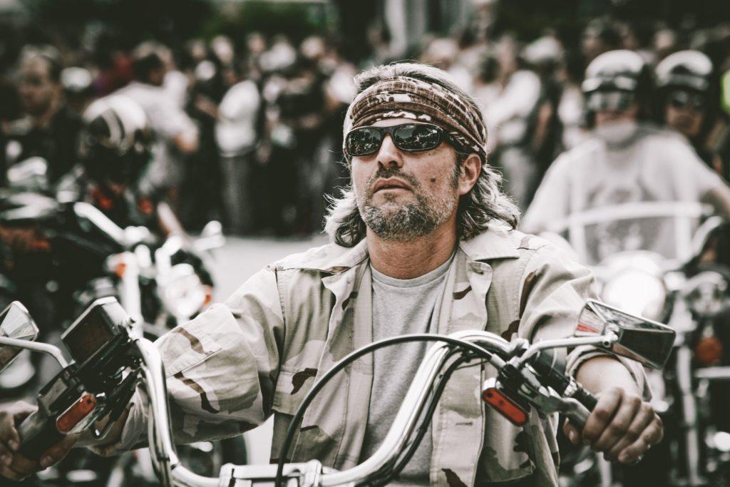 Harleysta: in primo piano un motociclista, con giubbotto di jenas grigio e occhiali da sole