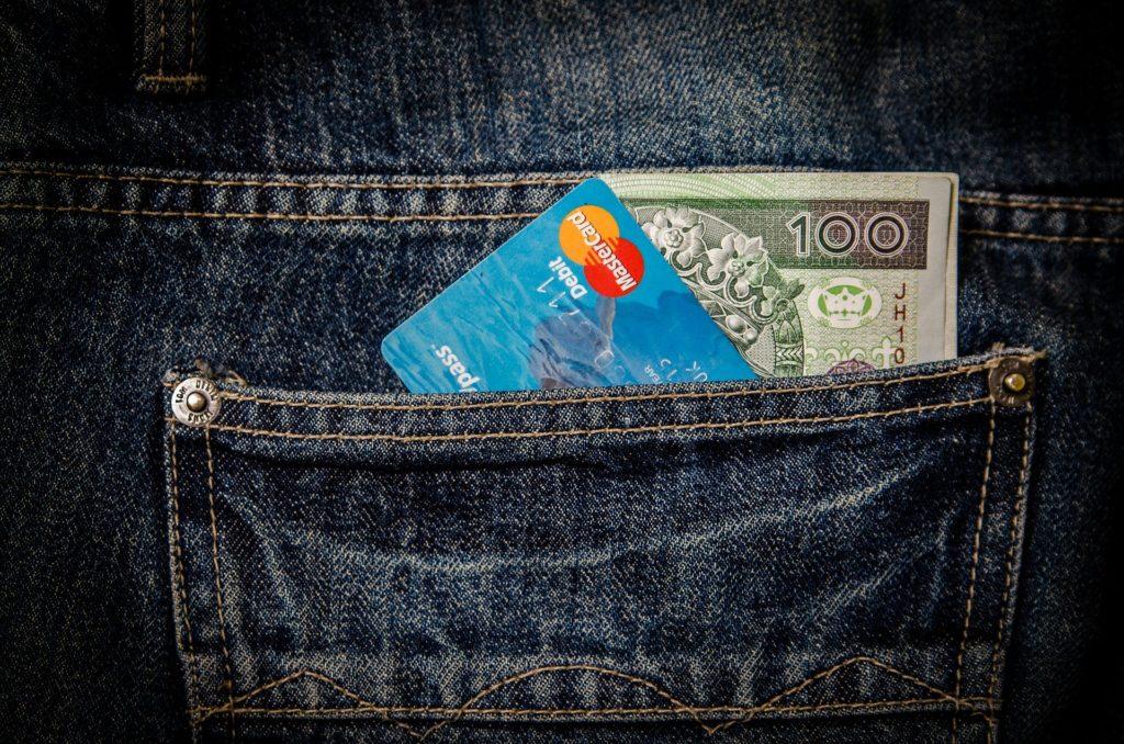 una tasca di un jeans dalla quale spuntano una carta di credito e dei soldi sindrome da shopping