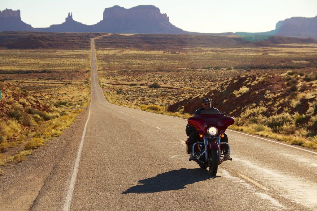 Harleysta: nella foto una highway americana in mezzo al deserto, con in primo piano una moto Harley-Davidson