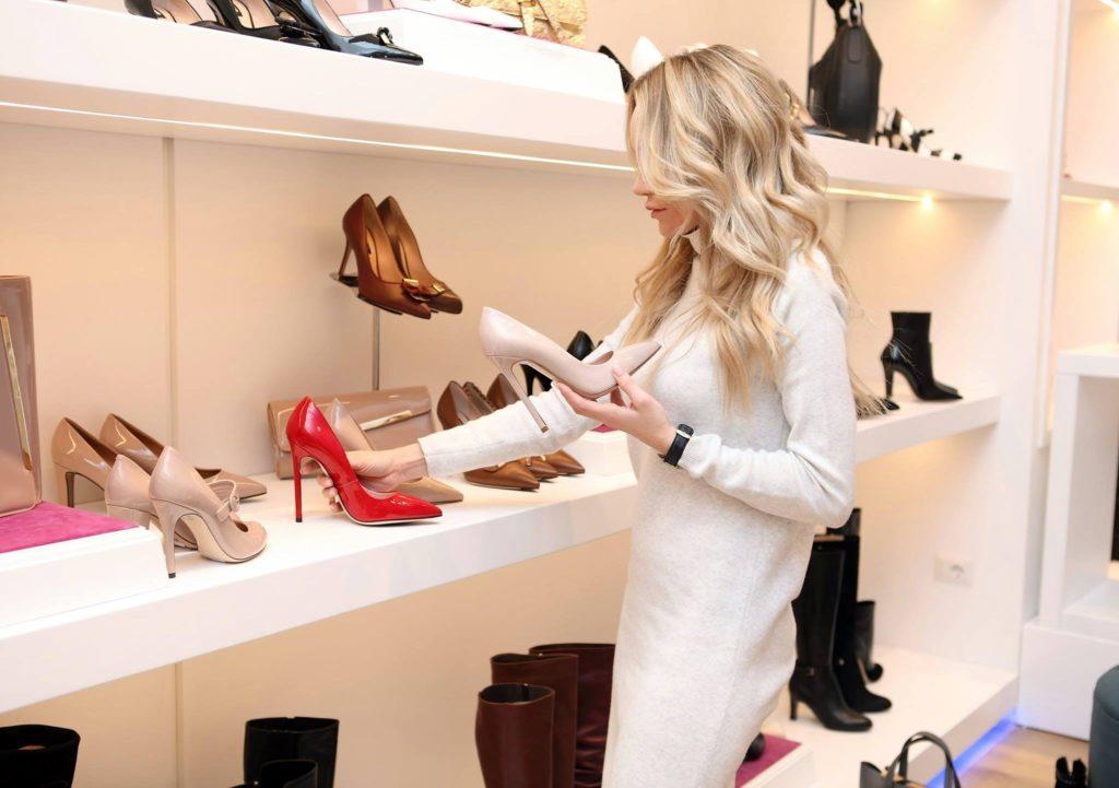 Una donna vestita di bianco sta scegliendo delle scarpe in offerta black friday su uno scaffale di un negozio
