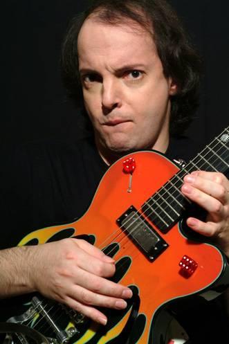 Dado, comico di Zelig e Colorado, mentre suona una chitarra arancione con due dadi rossi incollati, su sfondo nero