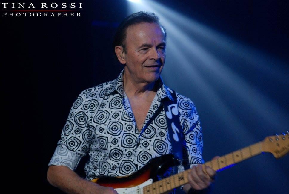 Dodi Battaglia con camicia a fantasia suona la chitarra