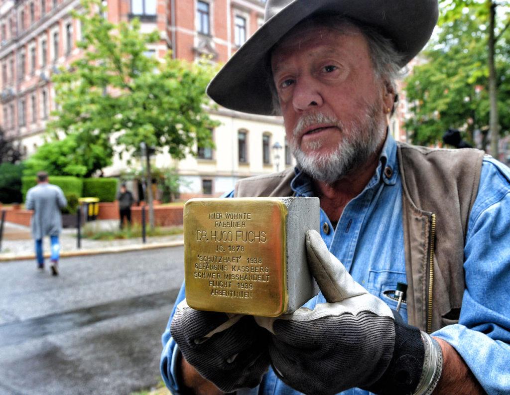 Gunter Demnig che mostra una pietra di inciampo incisa con la targa in ottone