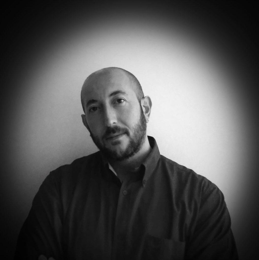 Antonello Spadafora in una foto in bianco e nero, indossa una camicia nera, con la testa inclinata da un lato