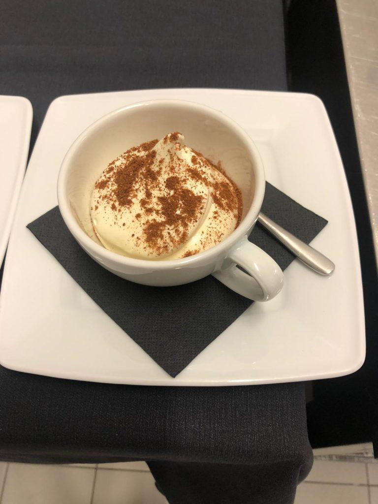 Sul tacolo di cucina dello chef Luca Pieroni, un dolce in tazza con polvere di cioccolato