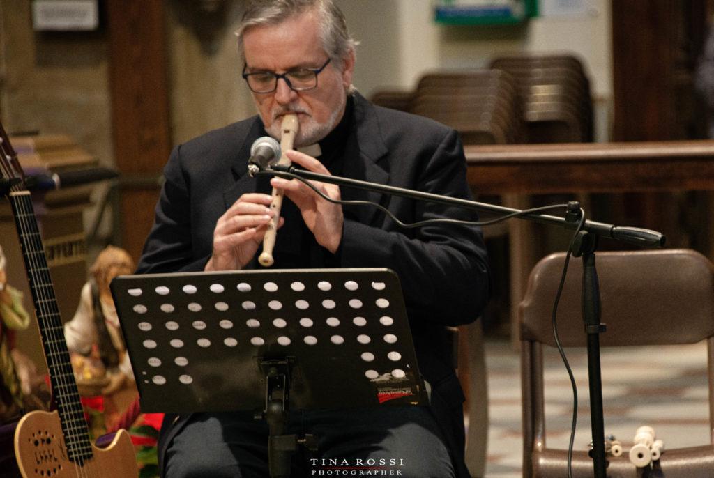 Don Carlo fonde insieme Chiesa e musica suonando un flauto seduto davanti a un leggio, come discusso nel convegno pontificio di novembre