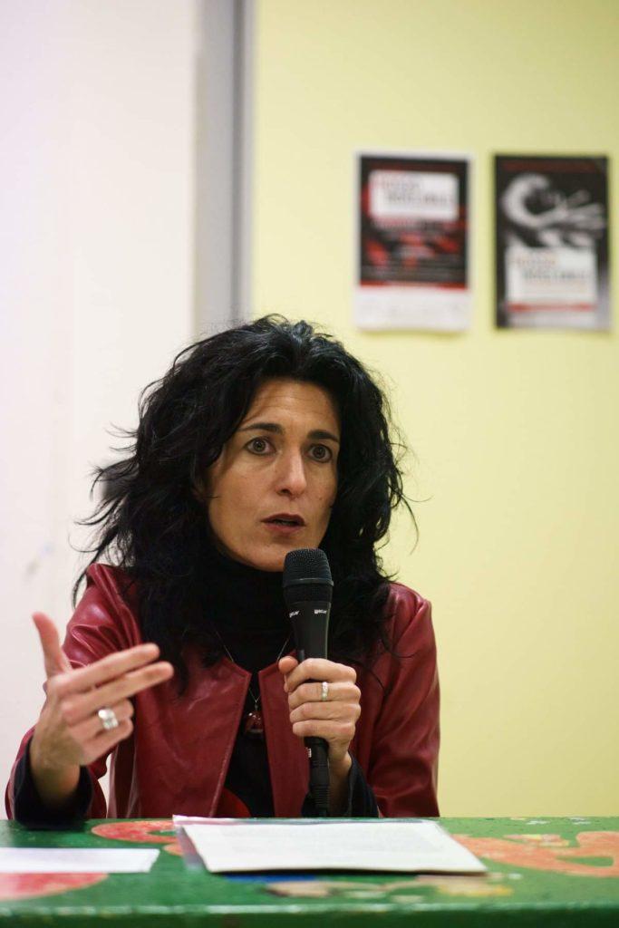 La psicologa Henni Rissone spiega la pulsione alla violenza. Giubbotto rosso seduta al tavolo durante un convegno