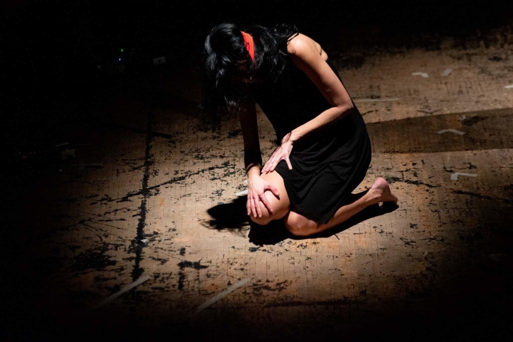 Performance contro la violenza di Muta la pelle. Progetto rosso indelebile. Ina donna accovacciata sul palco con una benda rossa sugli occhi