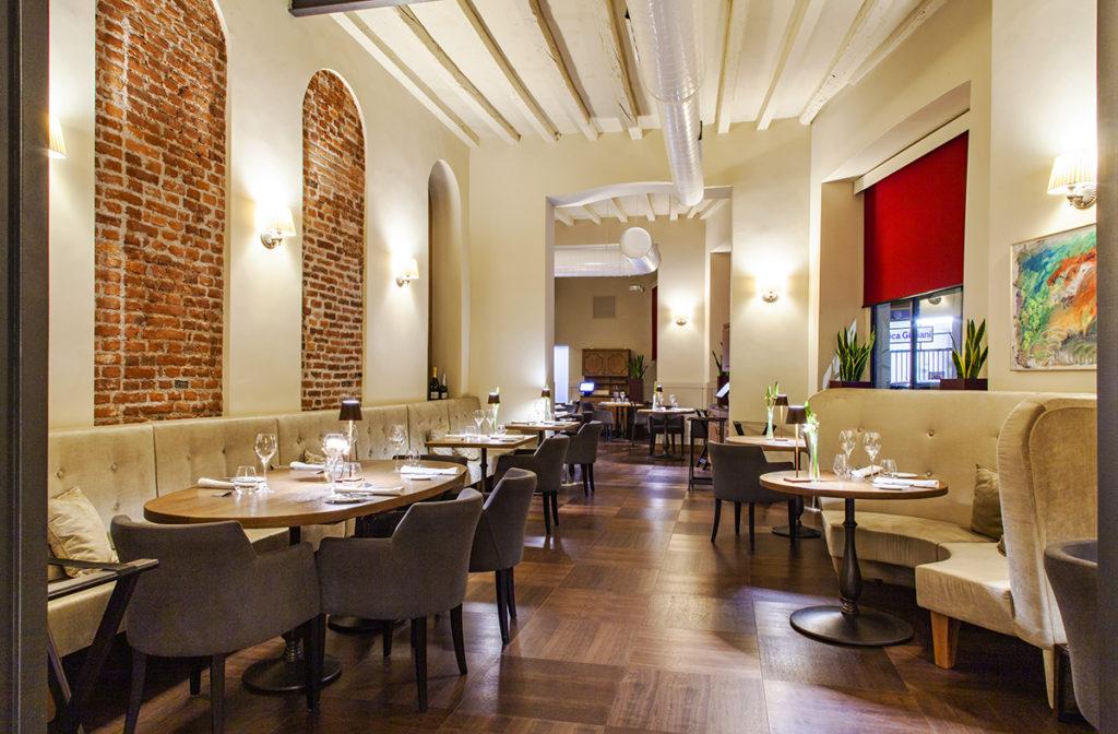 Gli interni del ristorante L'Alchimia, dei divanetti a semi cerchio su un lato del corridoio, con tavolini apparecchiati, e divani dritti lungo la parete sull'altro lato
