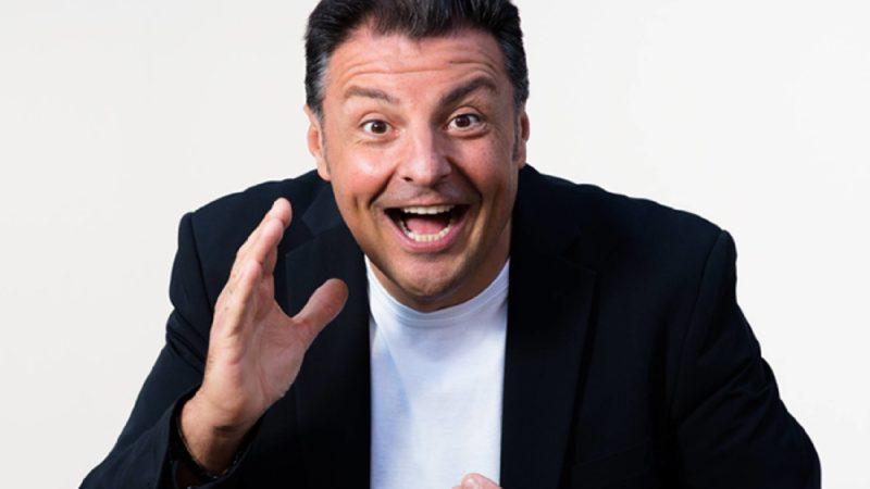 Claudio Lauretta ha una mano sollevata in alto verso il viso e la bocca aperta, probabilmente sta parlando mentre imita qualcuno, indossa una maglietta bianca e una giacca nera, su sfondo bianco