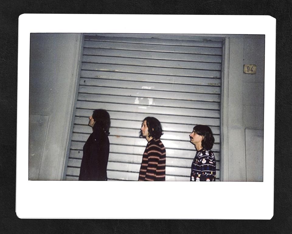 i tre musicisti della band osaka flu in fila uno dietro l'altro girati di lato, sullo sfondo una serranda abbassata