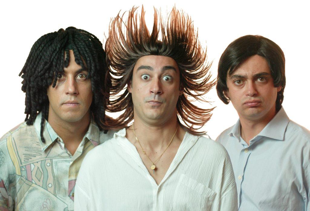 Pino e gli anticorpi, i tre personaggi comici, indossano tutti e tre una camicia bianca, con lo sguardo buffo e serio, su sfondo bianco, il personaggio in mezzo ha i capelli alzati