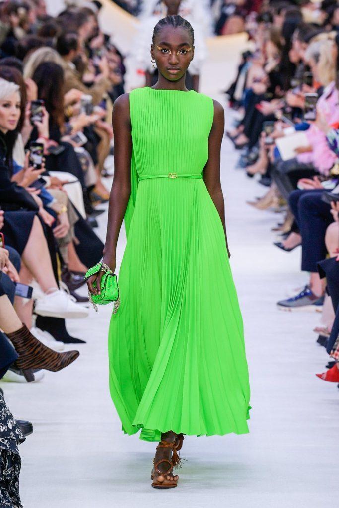 una modella vestita con abito verde lungo e sandali alla schiava pìnella sfilata fashion & style