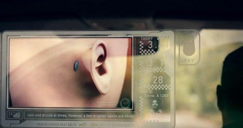 scena tratta dalla serie netflix black mirror, in un riquadro vi è la parte dietro della testa di un manichino come esempio, dietro l'orecchio fa vedere l'impianto, un piccolo chip blu