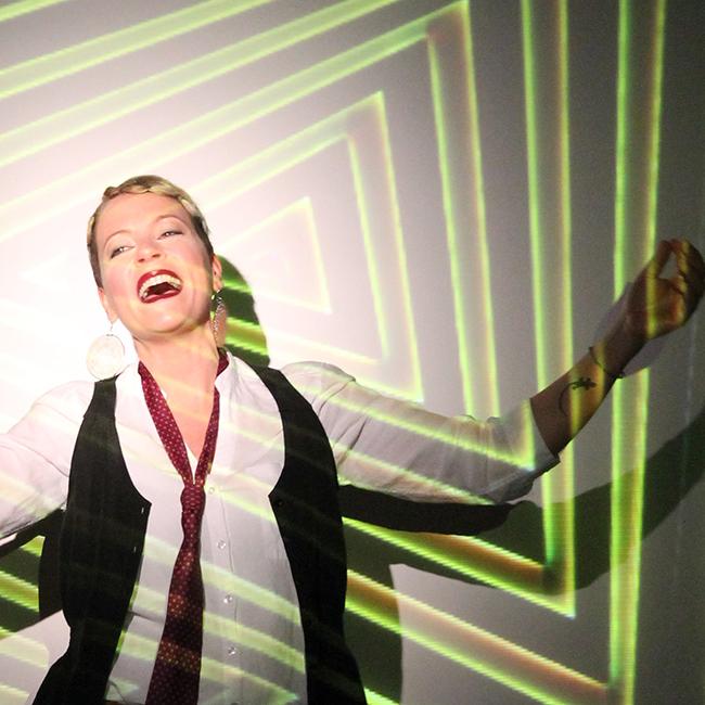 Claudia Cantisani, la jazzista italiana che si esibirà al Blue Note di Milano. Ha l'espressione felice, sorridente, con le braccia allargate, come se stesse ballando. Indossa una camicia bianca, gilet nero e cravatta rossa. Sullo sfondo un effetto di luci a triangoli verdi e marroni, incastrati uno dentro l'altro, che copre leggermente anche la cantante.