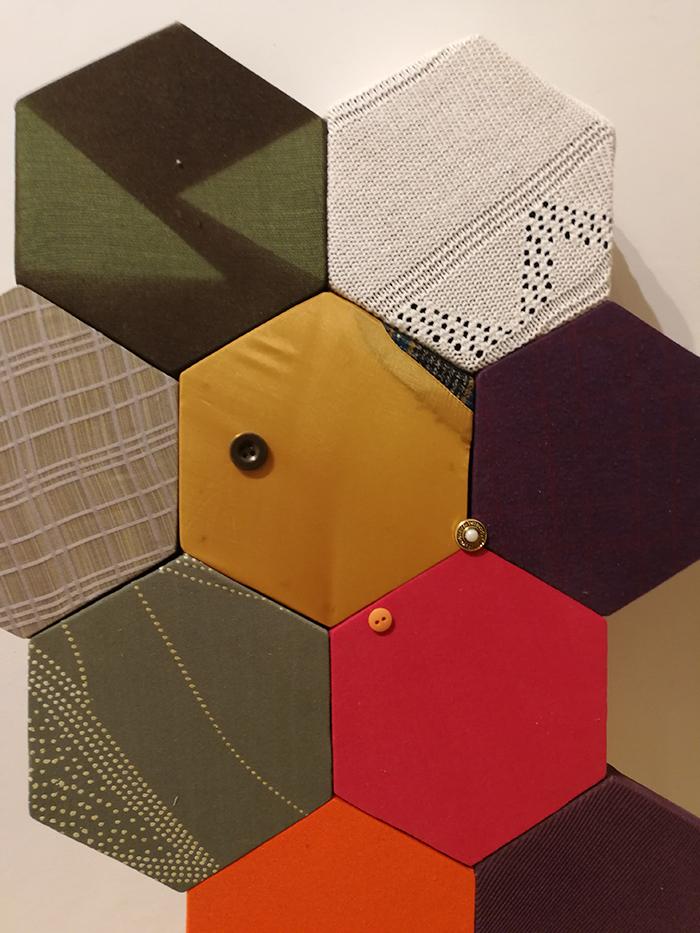 rappesentazione artistica di antonello spadafora, forme esagonali incastrate tra di loro di diversi colori e tessuti, tra cui rosso, verde, color crema, bordeaux e bianco