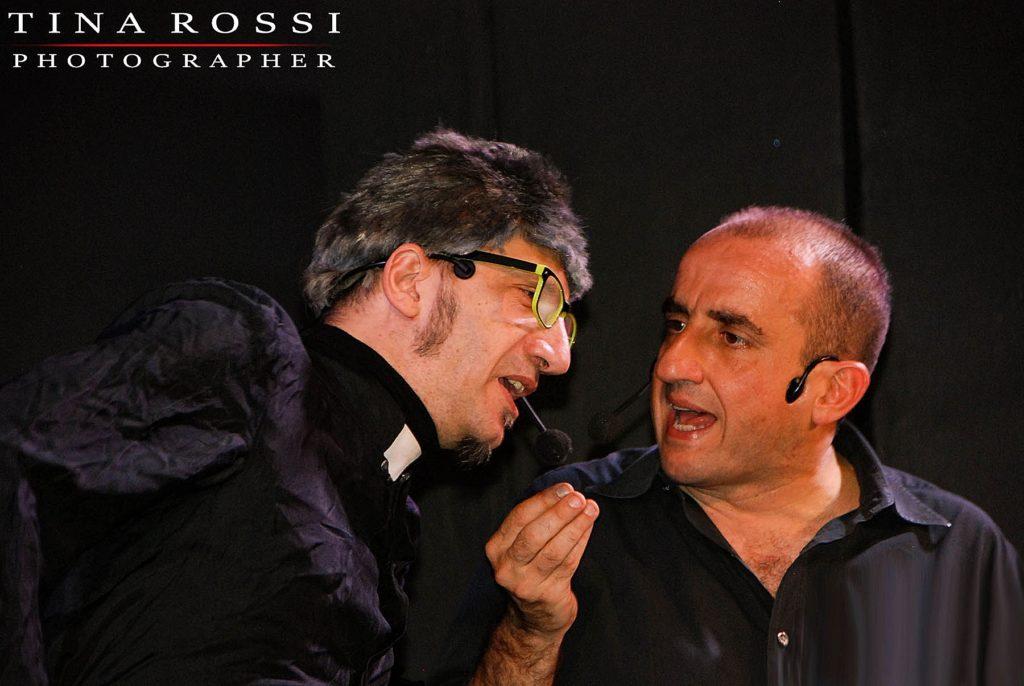Mauro Villata e Gianpiero Perone in scena durante uno sketch, a sinistra Villata, nelle vesti da frate, indossa un paio di occhiali da vista, a destra Perone con una mano alzata all'altezza del mento in mezzo ai due sta parlando con il comico, indossa una camicia nera, su sfondo nero, fotografia di Tina Rossi