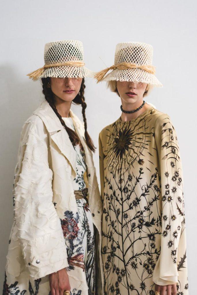 due modelle in fashion & style, vestite con cappelli do ìi paglia e abiti bianchi fioreggiati.
