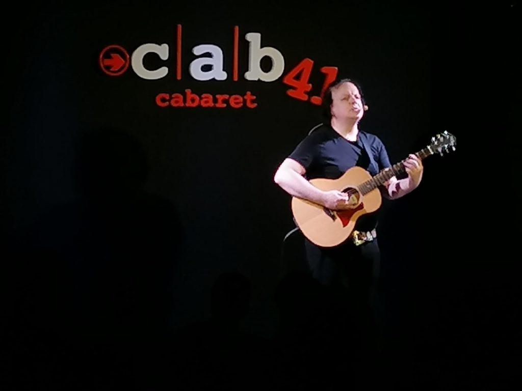 Dado, comico di Zelig e Colorado, su sfondo nero con il nome del locale Cab41, cabaret, suona la chitarra mentre sta cantando, indossa una maglietta a maniche corte nera