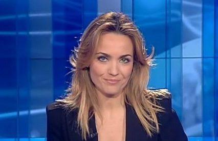 Laura Chimenti, candidata al ruolo di first lady al fianco di Amadeus, veste top bianco sotto giacca scura, con lunghi capelli biondi e viso sorridente