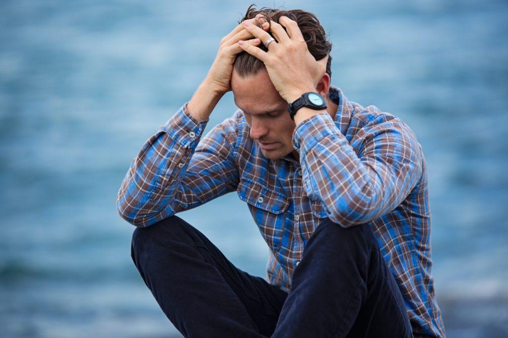 Legge salva suicidi: Un uomo seduto sul bordo del mare, in crisi, disperato con le mani nei capelli