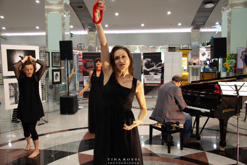 Rosalba Castelli nella performance per muta la pelle,  sulla violenza sulle donne,  vestita di nero tiene nela mano alzata un fazzoletto rosso