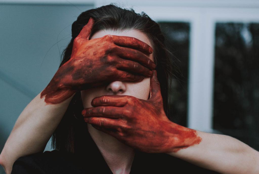 muta la pelle il titolo di questa foto dove due mani sporche di sangue chiudono gli occhi e la bocca di una donna
